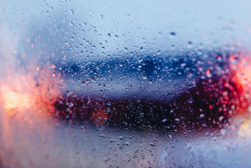 Camino de ciudad de la noche con descenso abstracto del agua del fondo de los coches del parabrisas en las luces y la lluvia de c fotografía de archivo libre de regalías