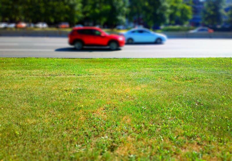Camino de ciudad vacío con tráfico y fondo de la hierba verde imagenes de archivo