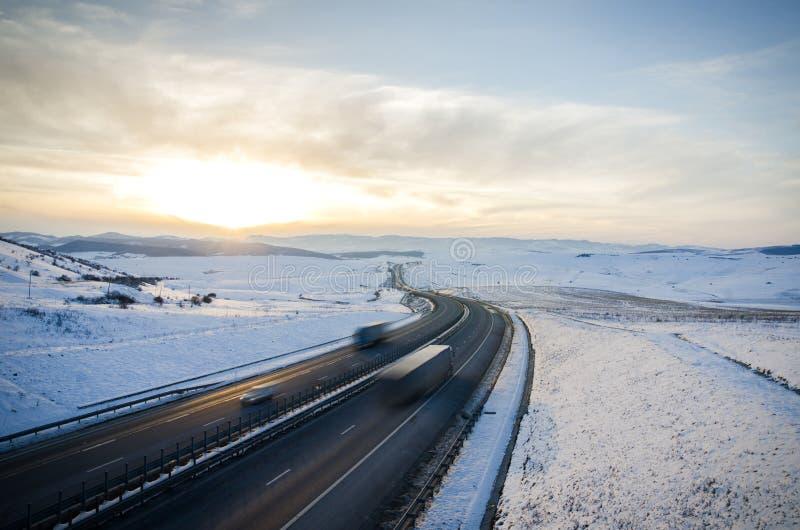 Camino de la carretera sobre las montañas con los coches que apresuran y los camiones encendido fotografía de archivo
