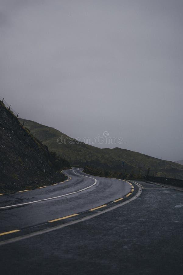 Camino de la carretera de Two-laned que pasa a través de las montañas con las líneas de restricción amarillas dobles imagenes de archivo