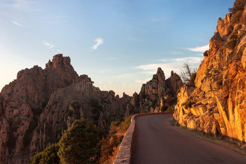 Camino de la montaña con las rocas en la puesta del sol Camino de la montaña con el acantilado de la luz del sol fotografía de archivo