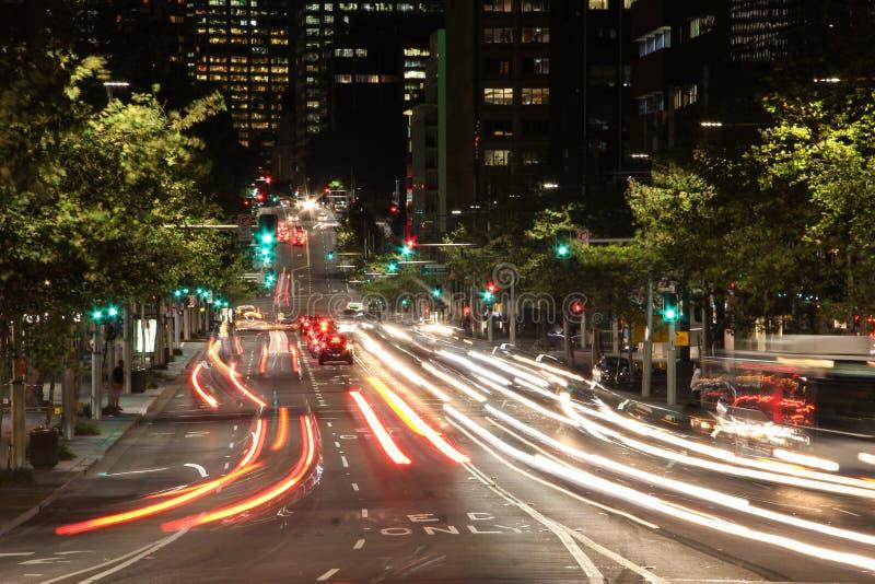 Camino de la noche con las luces borrosas de coches fotografía de archivo