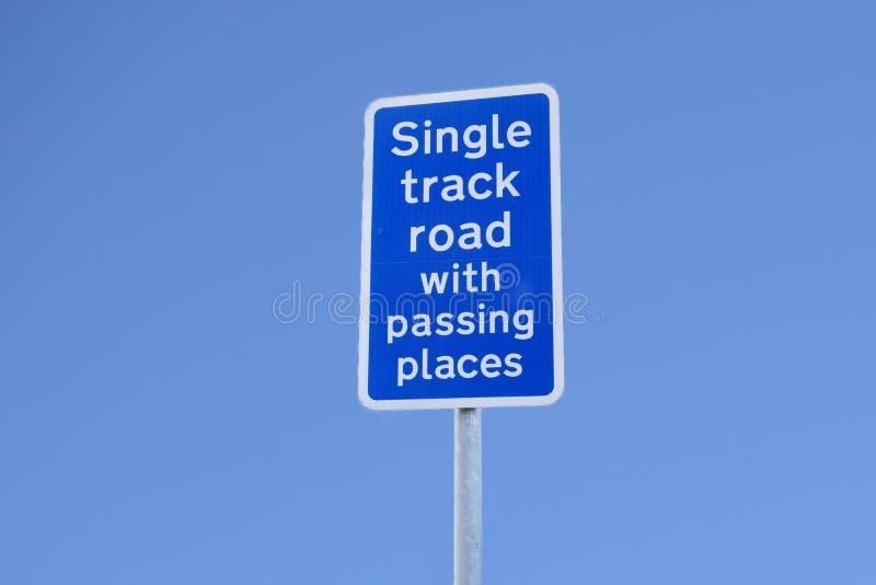 Camino de la sola pista con el paso del poste de muestra de los lugares contra el cielo azul fotografía de archivo