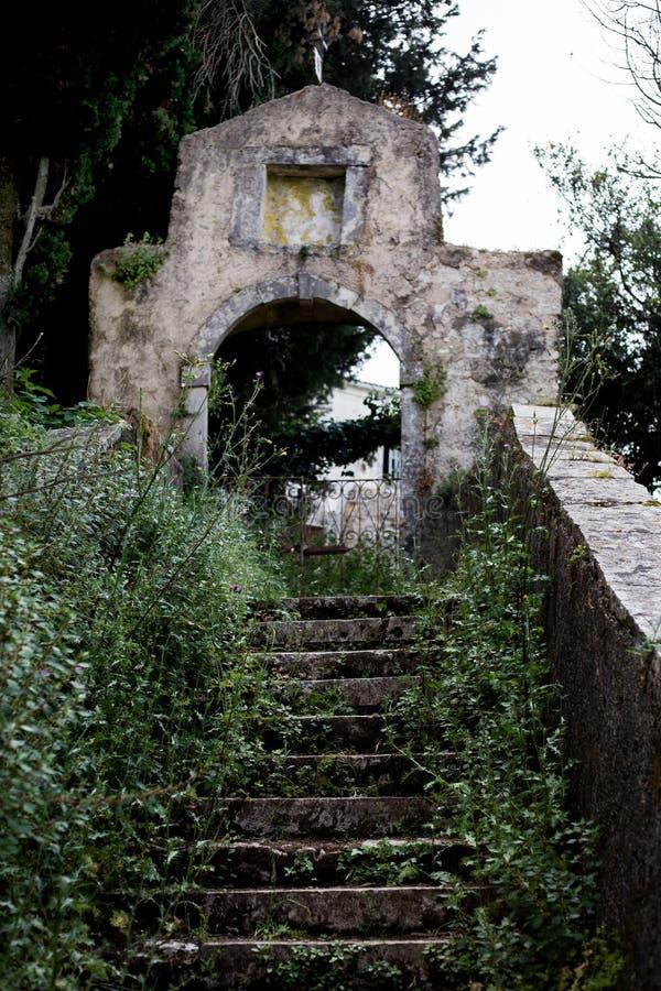Camino de paso arquitectónico de la edad avanzada carismática a un edificio acient Las escaleras se cubren ya con las hierbas y l fotografía de archivo