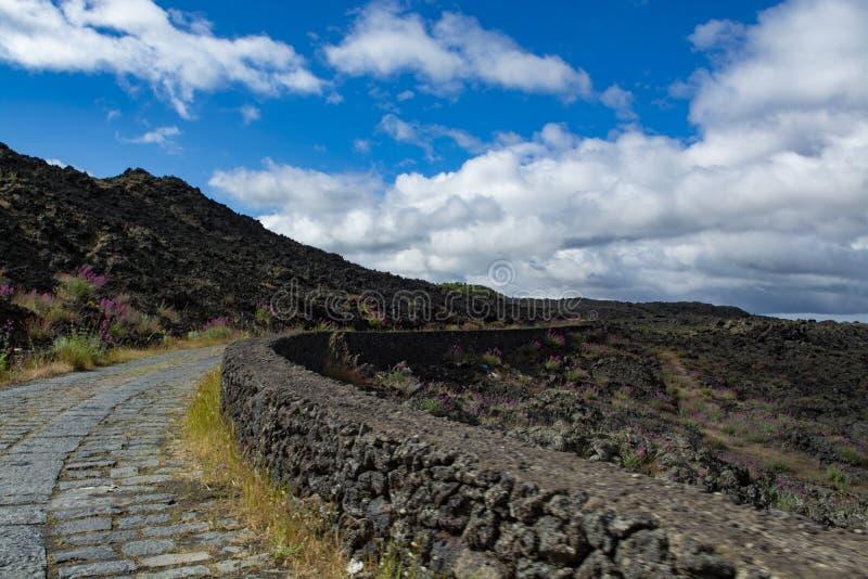 Camino de piedra a través de campos de lava negros en las cuestas del volcán del monte Etna, acceso del coche al parque nacional  imagenes de archivo