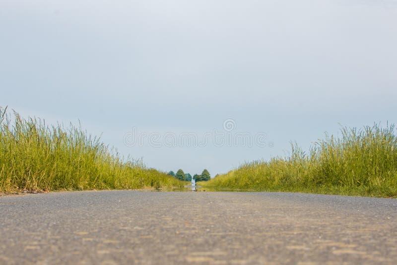 Camino de tierra con el camino pavimentado fotografía de archivo libre de regalías
