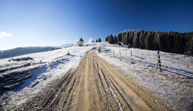Camino de tierra del invierno en el top de las colinas imagen de archivo libre de regalías
