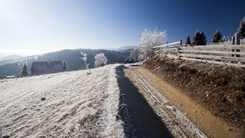 Camino de tierra del invierno en el top de las colinas foto de archivo libre de regalías