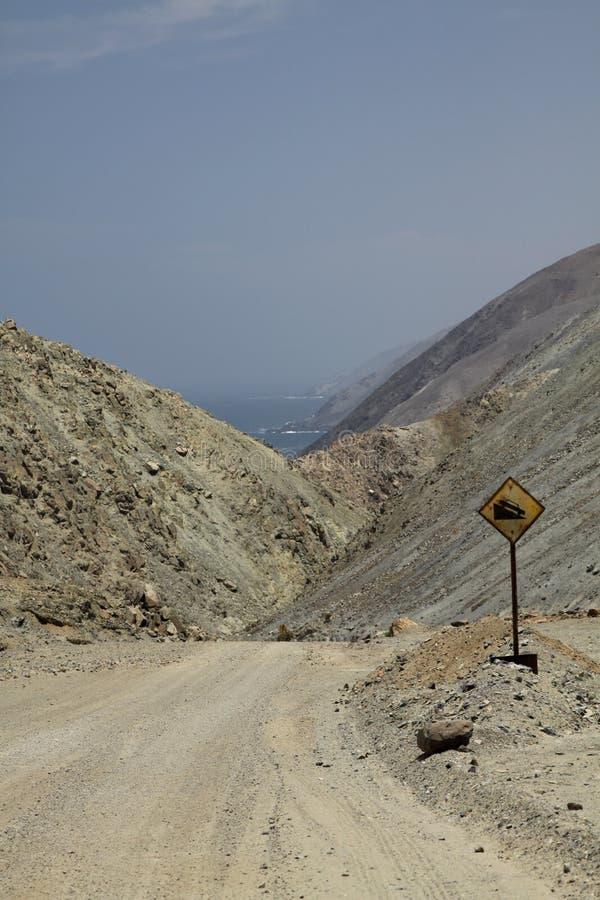 Camino de tierra que lleva cuesta abajo con paisaje estéril rocoso a la Costa del Pacífico en el desierto de Atacama, Chile imagen de archivo