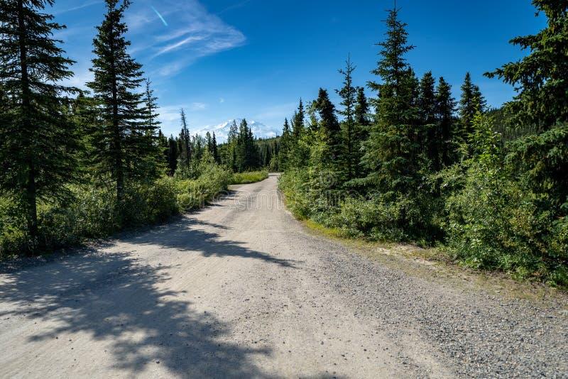 Camino de tierra que lleva para preguntarse el lago en el parque nacional de Denali Mt Denali McKinley en el fondo, visión clara imagen de archivo