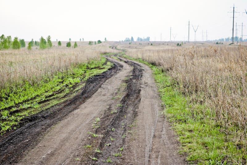 Camino de tierra quebrado sucio entre los campos en primavera temprana El concepto de viaje imagen de archivo libre de regalías