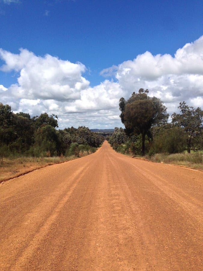 Camino de tierra recto que estira a través de campo australiano imagen de archivo libre de regalías