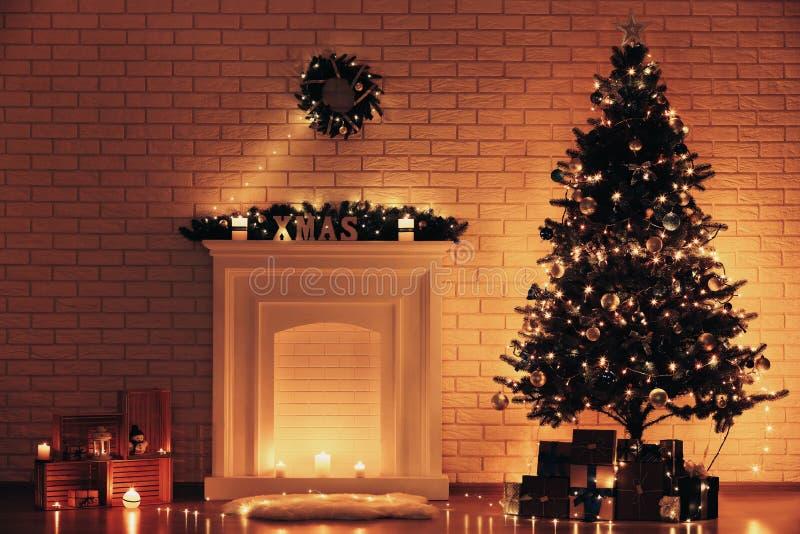 Camino decorato vicino all'albero di Natale fotografia stock