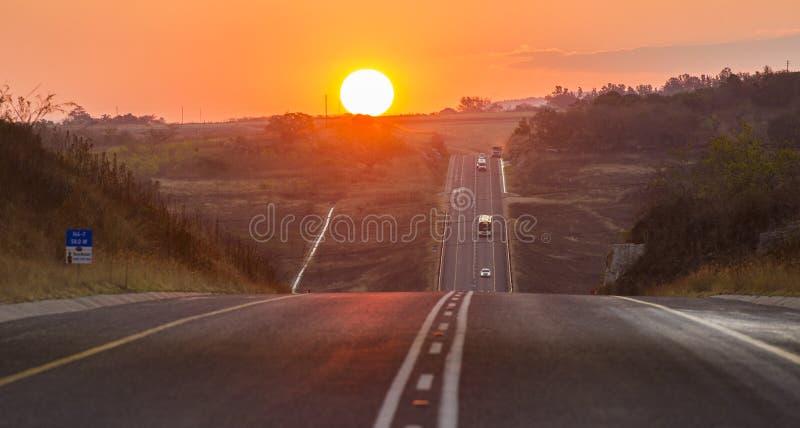 Camino del alquitrán del asfalto en la puesta del sol en Suráfrica imagen de archivo