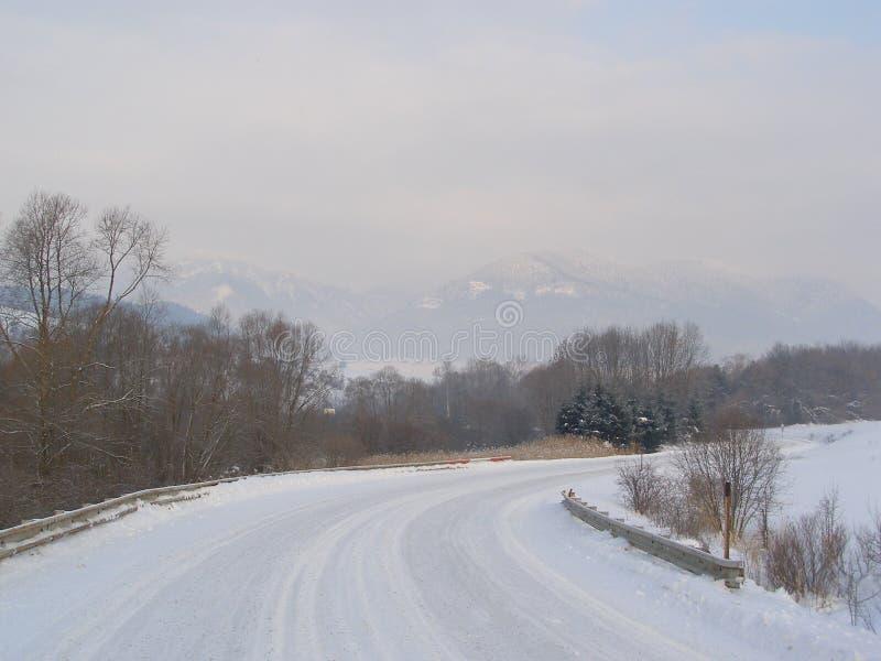 Camino del invierno en Eslovaquia con las montañas a continuación imagenes de archivo