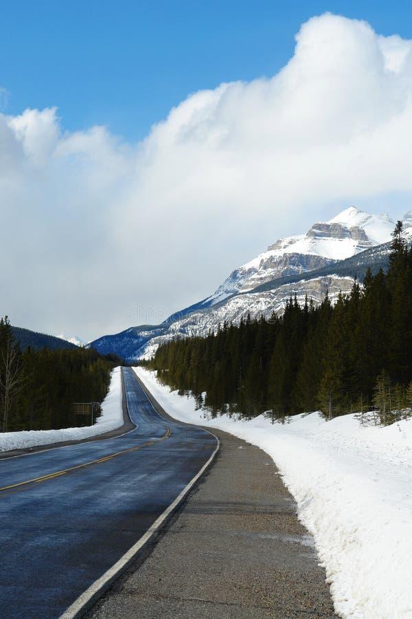 camino del invierno en montañas rocosas fotos de archivo