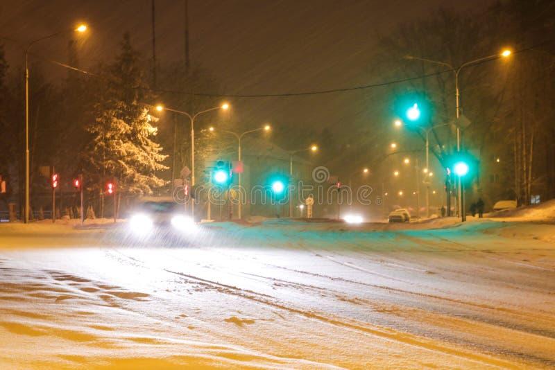 Camino del invierno Nevado con la conducción de automóviles en el camino en tormenta de la nieve fotos de archivo libres de regalías