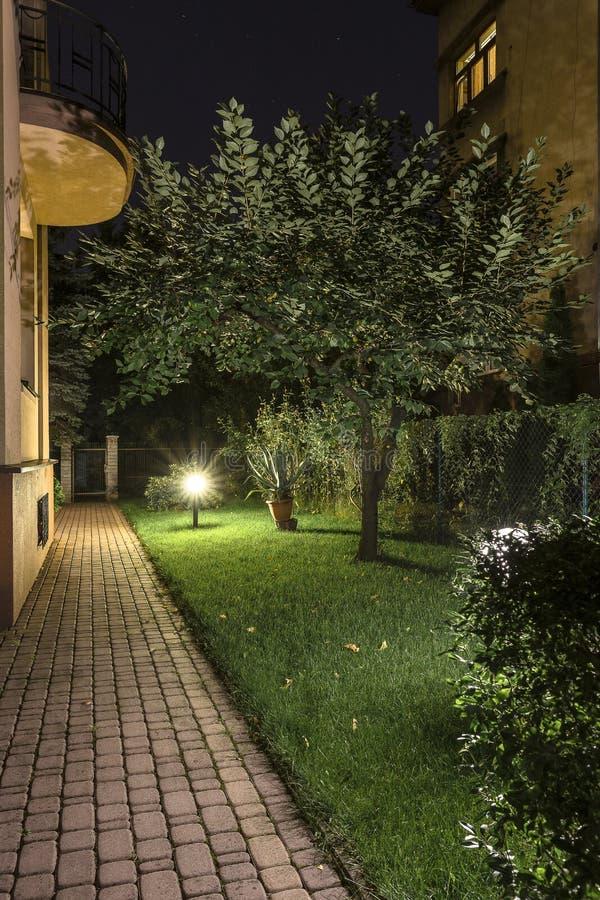 Camino del jardín del patio trasero en la noche fotos de archivo