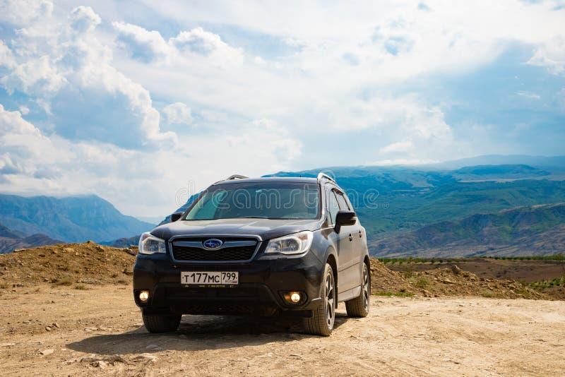 Camino del pilar del coche del silvicultor de Subaru en tierra seca del desierto en montañas en el cielo azul fotografía de archivo libre de regalías