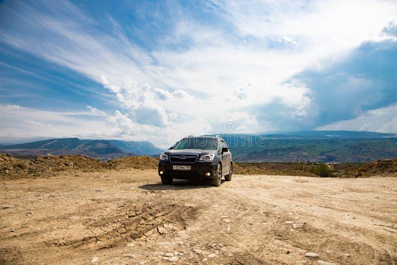Camino del pilar del coche del silvicultor de Subaru en tierra seca del desierto en montañas en el cielo azul imagenes de archivo