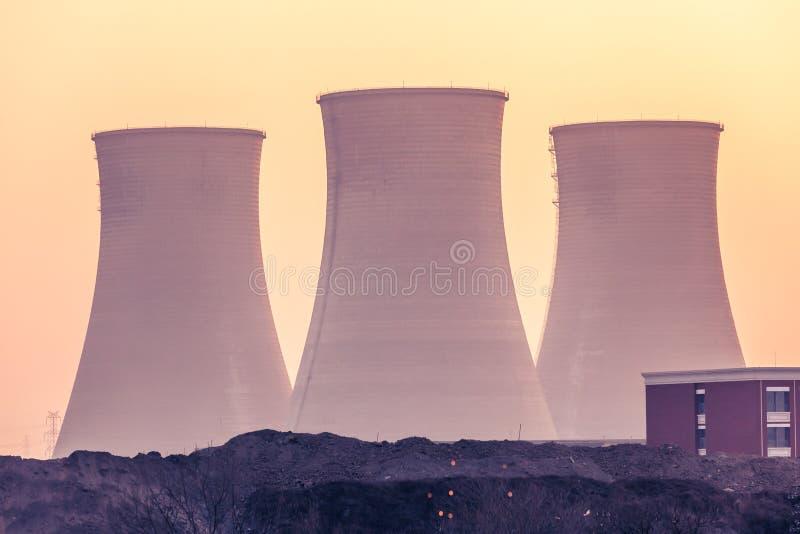Camino e torri di raffreddamento della centrale elettrica durante il tramonto fotografia stock
