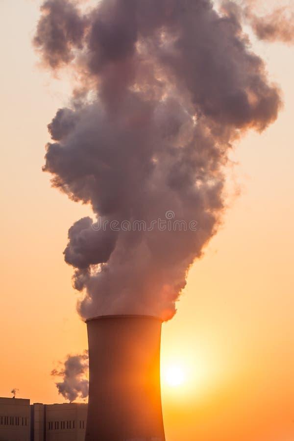 Camino e torri di raffreddamento della centrale elettrica durante il tramonto fotografia stock libera da diritti
