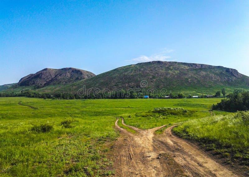Camino en el paisaje brillante de los colores del cielo azul de la hierba verde de las montañas del pueblo foto de archivo libre de regalías