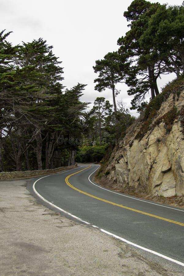 Camino en una carretera costera en un día cubierto foto de archivo