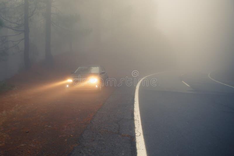 Camino forestal y coche densos de la niebla en el borde de la carretera con los haces luminosos imagenes de archivo