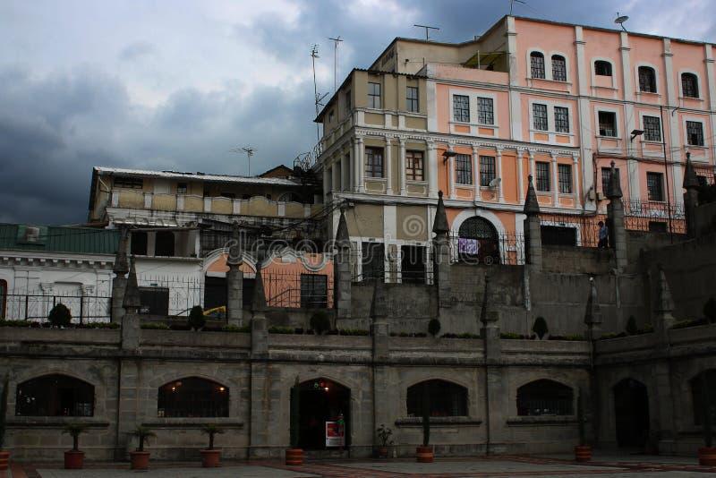 Camino gris oscuro y sucio con los edificios coloridos en el fondo y un cielo oscuro por completo de nubes en Quito Ecuador imagen de archivo libre de regalías