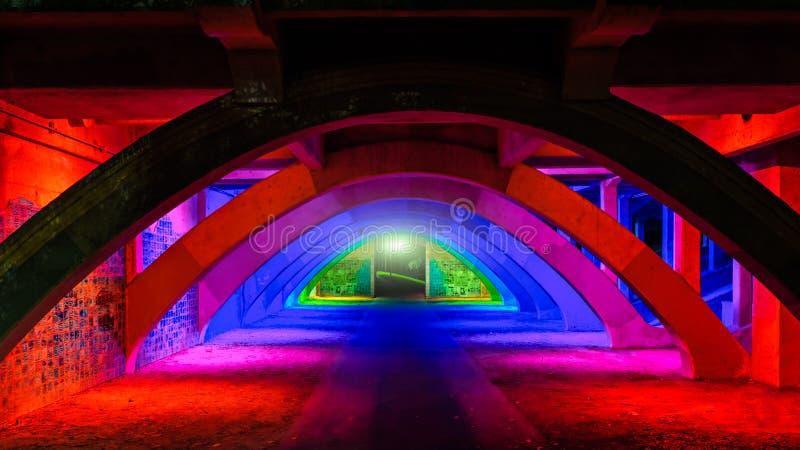 Camino iluminado colorido debajo del puente imagenes de archivo