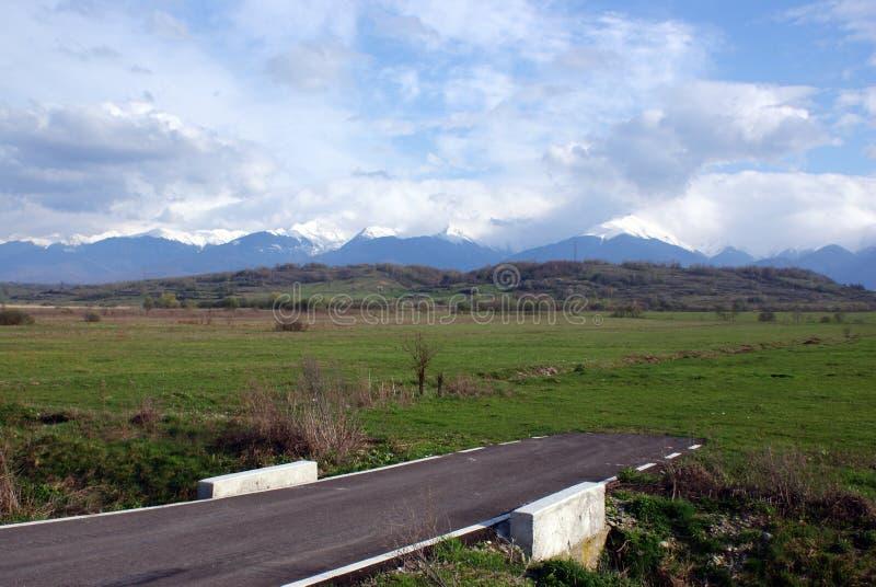 Camino inacabado a las montañas foto de archivo