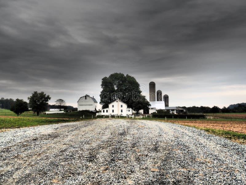 Camino a la granja del país con el cielo dramático fotografía de archivo libre de regalías