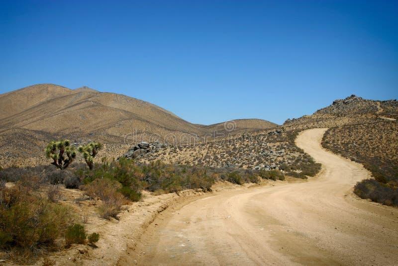 Camino largo, ventoso en el desierto imagen de archivo