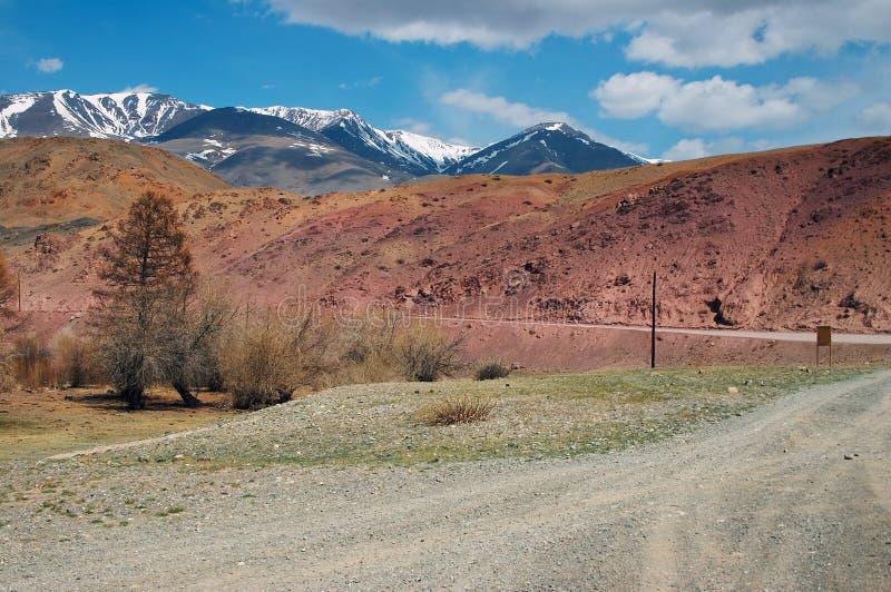 Camino, montañas rojas y cielos azules fotografía de archivo