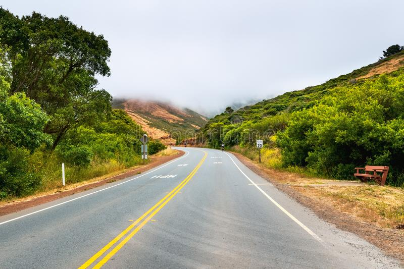 Camino pavimentado con un límite de velocidad de 35 mph que pasa a través de Marin Headlands; día nublado y de niebla; Marin Coun imagen de archivo