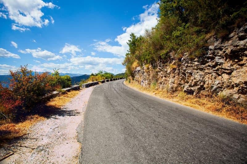 Camino pavimentado en las montañas lejos fotos de archivo