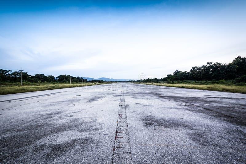 Camino/pista vieja clara y cielo azul nublado imagen de archivo