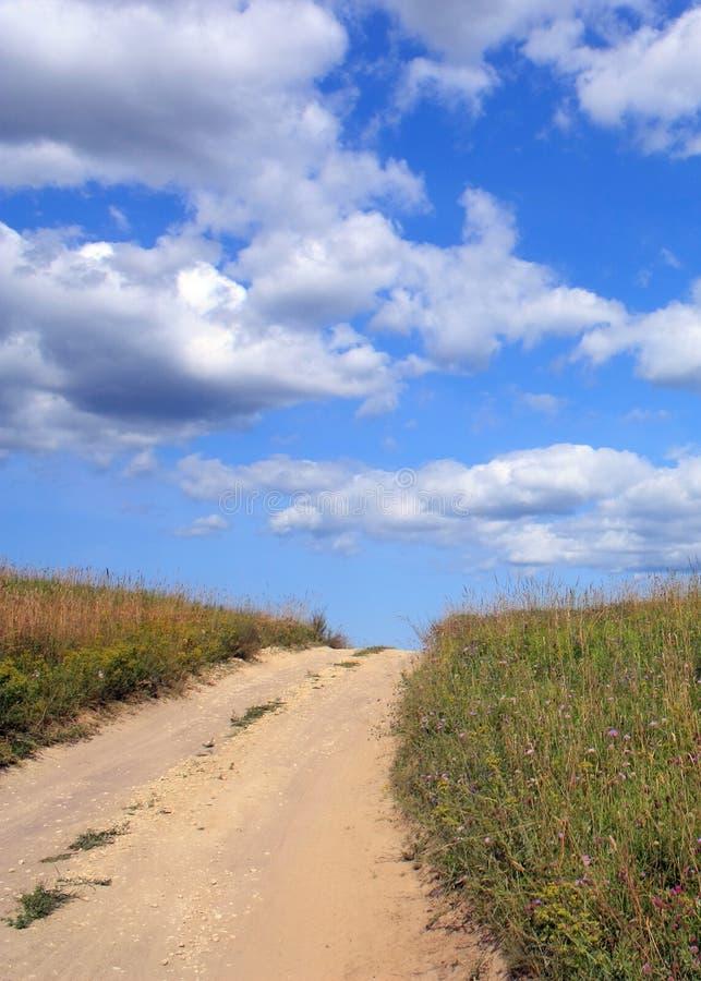 Camino, prado y cielo fotografía de archivo libre de regalías