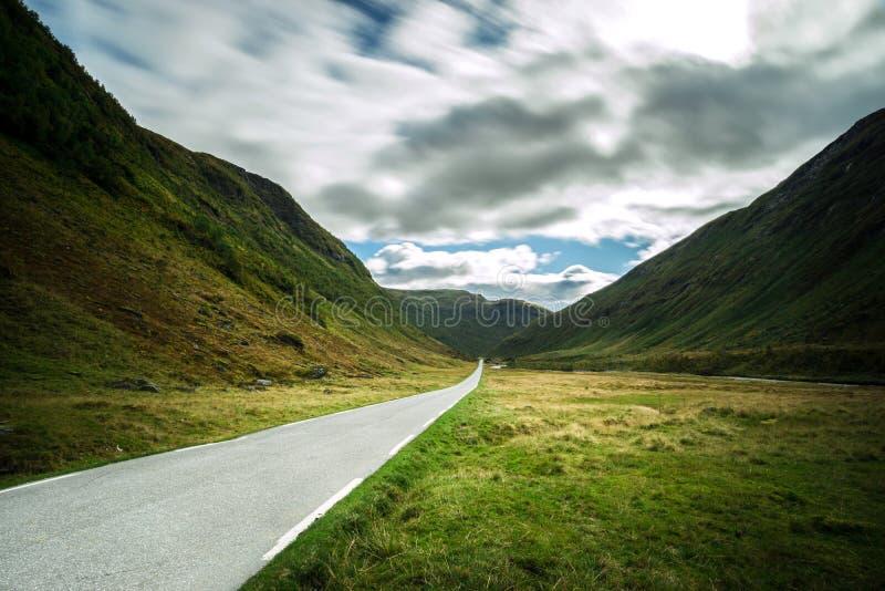 Camino recto de la montaña que lleva a través del valle dramático, Noruega imagen de archivo libre de regalías