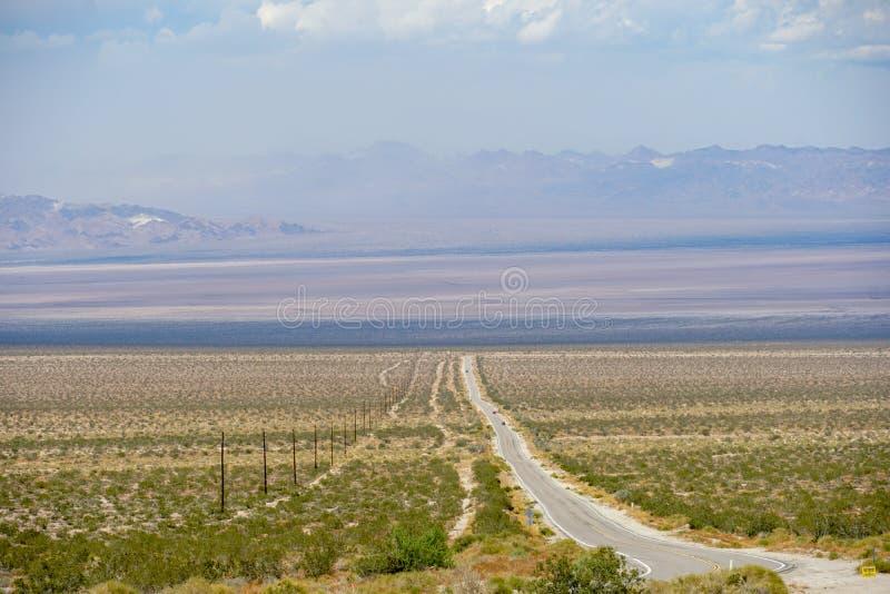 Camino recto Joshua Tree Park siguiente del desierto sin fin fotos de archivo