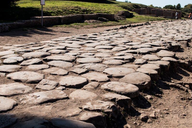 Camino romano antiguo pavimentado con las piedras para el carro Decumano maxi imagenes de archivo