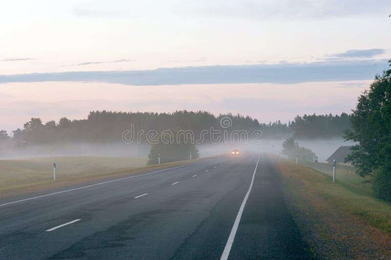 Camino rural con las linternas del coche que aparecen a través de la niebla imagenes de archivo