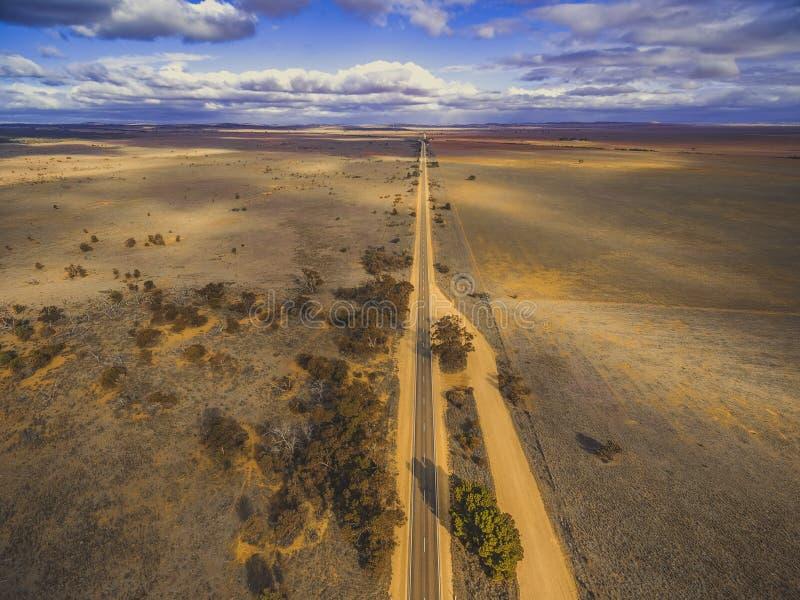 Camino rural recto que pasa a través de los llanos imágenes de archivo libres de regalías