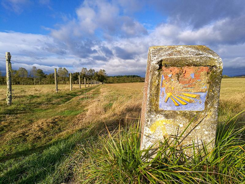 Camino Santiago de Compostela - traditional camino shell symbol on milestone. Old traditional camino yellow shell symbol on milestone on autumn Spanish pasture royalty free stock images