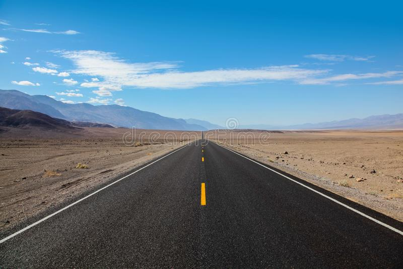 Camino sin fin y solo del blacktop que entra la cordillera que entra en el parque nacional de Death Valley fotografía de archivo libre de regalías