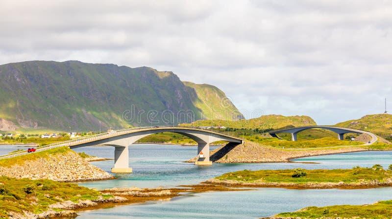 Camino torcido de la carretera con los puentes de Freedvang en el fiordo, isla de Lofoten, condado de Nordland del municipio de F imagen de archivo libre de regalías