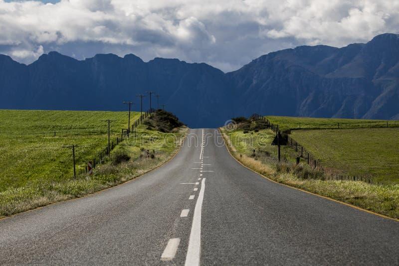 Camino a través de campos agrícolas con la cordillera en la distancia - Somerset West, Western Cape, Suráfrica fotografía de archivo