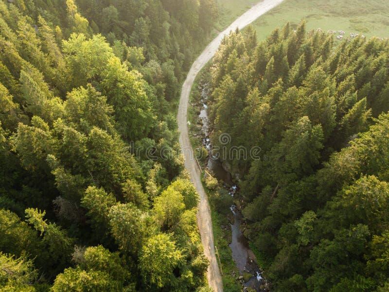 Camino a través de las montañas y bosque capturado desde arriba foto de archivo libre de regalías