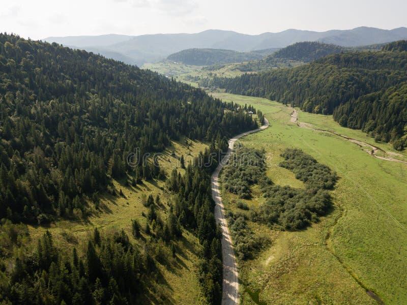 Camino a través de las montañas y bosque capturado desde arriba imagenes de archivo
